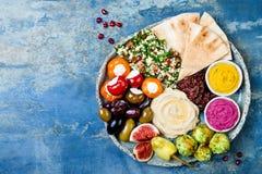 De mezeschotel van het Middenoosten met groene falafel, pitabroodje, in de zon gedroogde tomaten, pompoen, bietenhummus, olijven, Stock Afbeelding