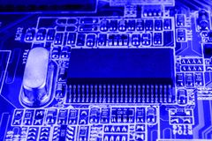 De microchip en het kwarts op motherboard van een moderne computer blauwe achtergrond sluiten macro Royalty-vrije Stock Afbeeldingen