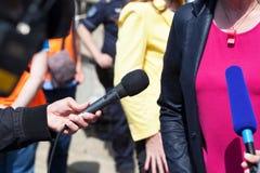 De microfoon die van de journalistholding televisiegesprek leiden Stock Afbeeldingen