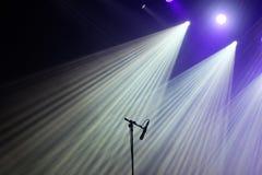 De microfoon en de heldere stralen van licht op stadium vóór het overleg beginnen stock afbeelding