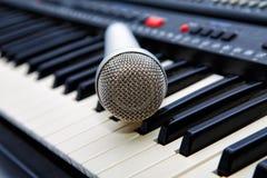 De microfoon ligt op de synthesizer Stock Afbeelding
