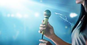 De microfoon van de vrouwenholding en het zingen op de achtergrond van het overlegstadium stock foto