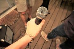 De microfoon van de handholding bij partij royalty-vrije stock fotografie