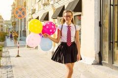 De de middelbare schoolstudent van de meisjestiener met ballons, in school eenvormig met glazen gaat langs de stadsstraat stock fotografie
