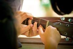De de middelbare schoolstudenten leren hoe te om gitaar in sch te spelen stock afbeeldingen