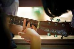 De de middelbare schoolstudenten leren hoe te om gitaar in sch te spelen stock fotografie