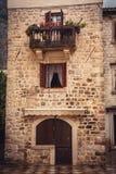 De middeleeuwse de bouwvoorgevel met oude houten deur opende venster en balkon met bloemen in oude Europese stad Kotor in Montene Royalty-vrije Stock Foto