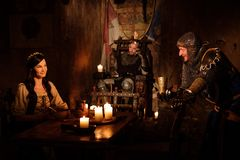 De middeleeuwse koning en zijn onderwerpen communiceren in de zaal van het kasteel Royalty-vrije Stock Foto's