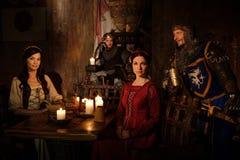 De middeleeuwse koning en zijn onderwerpen communiceren in de zaal van het kasteel stock afbeeldingen