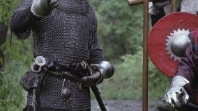 De middeleeuwse militair in chainmailpantser zet zijn zwaard in de schede stock video