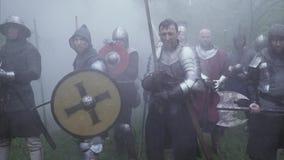 De middeleeuwse militairen in metaalpantser bevinden zich met hun uit wapens stock videobeelden