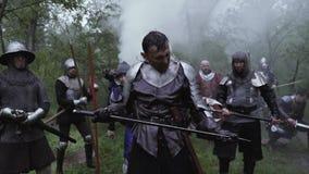 De middeleeuwse militairen zijn klaar voor de slag in het bos onder regen stock video