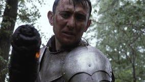 De middeleeuwse ridder in pantser treft voorbereidingen om de lijken na de slag te branden stock video