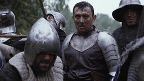 De middeleeuwse ridder in plaatpantser bevindt zich in het midden van het slagveld stock footage