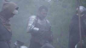 De middeleeuwse ridder zet zijn zwaard in schede na de slag, veel rook stock footage