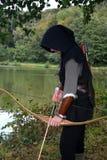 De middeleeuwse schutter met zwarte kap bevindt zich met gespannen kromme en pijl op water Stock Afbeeldingen