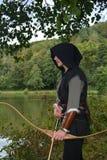 De middeleeuwse schutter met zwarte kap bevindt zich met gespannen kromme en pijl op water Stock Fotografie