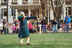 De middeleeuwse schutter schiet een pijl van een boog Wederopbouw van een middeleeuwse slag op het gebied van de schoolvoetbal stock foto's