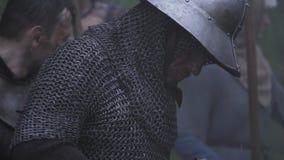 De middeleeuwse strijder met metaalhelm zet zijn zwaard in schede, onder regen stock video
