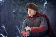 De middeleeuwse strijder in rode cloack houdt zwaard royalty-vrije stock afbeeldingen
