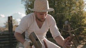 De middeleeuwse timmerman met de hamer en de beitel snijdt van hout stock video
