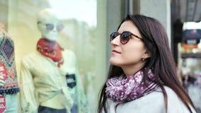 De middelgrote mooie vrouw die van de close-up enthousiaste koper showcase van boutique van openlucht bekijken stock videobeelden