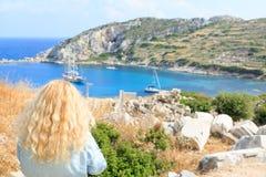 De Middellandse Zee van de blondevrouw met oude Griekse stadsruïnes stock foto