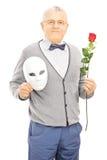 De midden oude herenholding nam bloem en masker toe Stock Fotografie
