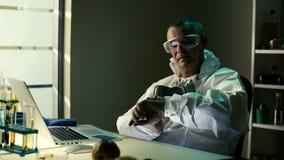 De midden oude hogere wetenschapper of de chemicus in beschermende kleren gaat CVC of CVV code in terwijl e-winkelend en betaalt  stock video