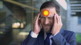De midden oude mens lijdt aan hoofdpijn, wijst de vlek migraine op pijn, close-up stock videobeelden
