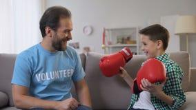De midden oude vrijwilligers gevende schooljongen bokshandschoenen, droom komen waar, sport stock footage