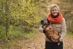 De midden oude vrouw is draagt de hond royalty-vrije stock afbeelding