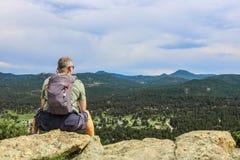 De midden oude zitting van de wandelaarmens op rots die horizon bekijken Royalty-vrije Stock Afbeeldingen