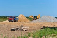 De mijnbouw, de vrachtwagen en het graafwerktuig van het steengroevezand naast een stapel van zand stock afbeeldingen
