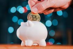 De mijnwerker die van Bitcoincryptocurrency BTC opnemen in piggy muntstukbank stock afbeeldingen