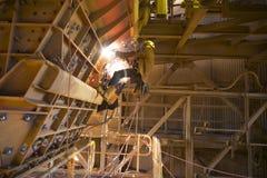 De mijnwerker die van de kabeltoegang de helm van de veiligheidsuitrusting het eenvormige werken bij hoogte aan kabel dragen die  stock foto
