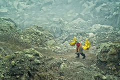 De mijnwerker draagt manden met zwavel in dampen van giftig vulkanisch gas van zwavelmijnen Stock Afbeeldingen