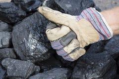 De mijnwerker toont steenkool met duimen omhoog op de achtergrond van steenkool royalty-vrije stock afbeelding