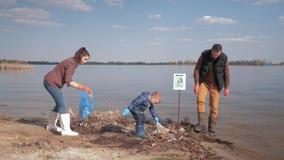 De milieuoplossingen, kindjongen helpt baren en maken de vader vrijwilligersactivisten vuile rivierkust van plastiek schoon stock videobeelden
