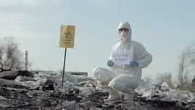 De milieuverontreiniging, Hazmat-mens in eenvormig toont teken sparen de planeet bij de stortplaats met wijzer biologisch gevaar stock video
