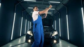 De militair danst dichtbij een auto met instrumenten in zijn handen stock footage
