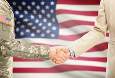 De militaire mens van de V.S. bij de eenvormige en burgerlijke mens in kostuum het schudden handen met adequate nationale vlag op stock fotografie