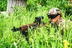 De militaire mensensluipschutter met automatisch geweer met een telescopisch gezicht ligt in gras in bos Royalty-vrije Stock Fotografie