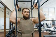 De militaire sport, spier Kaukasische gebaarde volwassen mens die oefeningen in de gymnastiek doen kleedde zich in een kogelvrij  royalty-vrije stock fotografie
