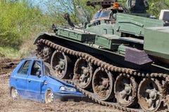 De militaire tank verplettert een blauwe auto Stock Afbeeldingen