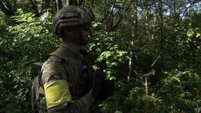 De militaire wapens zijn in het hout De militair beweegt zich bij de bos Bewapende man stock videobeelden