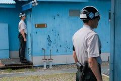 De militairen bevinden zich bij aandacht bij DMZ Stock Afbeeldingen