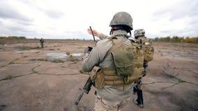 De militairen in eenvormig lopen over het gebied stock videobeelden