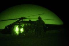 De militairen laden Helikopter bij Nacht Stock Foto's