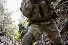 De militairen verkennen bos tijdens dag Stock Foto's